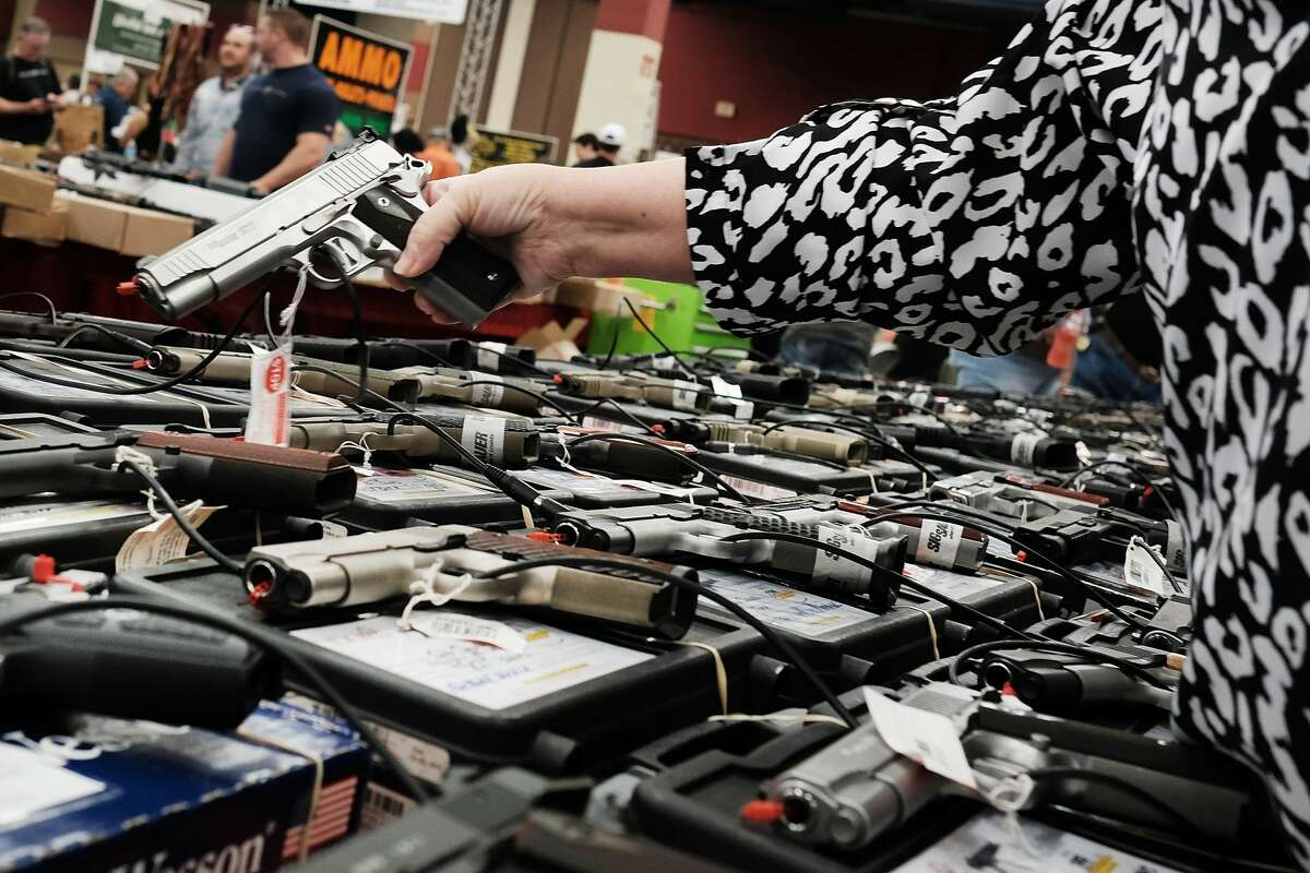 A woman tries a pistol at a gun show where thousands of different weapons are displayed for sale on July 10, 2016, in Fort Worth, Texas. The area is still mourning the deaths of five Dallas police officers on Thursday evening, July 7, 2016, by a lone gunman.
