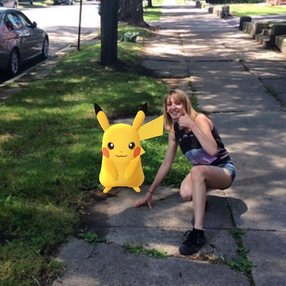 """Mary Zawacki, curator of the Schenectady County Historical Society, poses with a virtual Pikachu on the streets of the Stockade District. The """"augmented reality"""" game, which layers gameplay onto the physical world, became the top grossing app in the iPhone app store just days after its Wednesday release in the U.S., Australia and New Zealand. (Courtesy Photo)."""