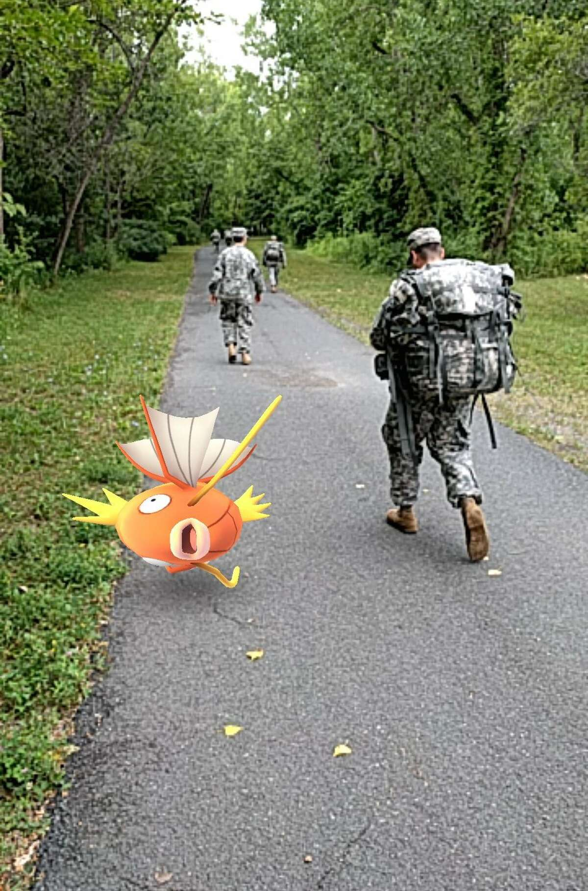 """National Guard soldier march past a virtual Magikarp over the weekend. The """"augmented reality"""" game Pokemon Go, which layers gameplay onto the physical world, became the top grossing app in the iPhone app store just days after its Wednesday release in the U.S., Australia and New Zealand. (Courtesy Photo)."""