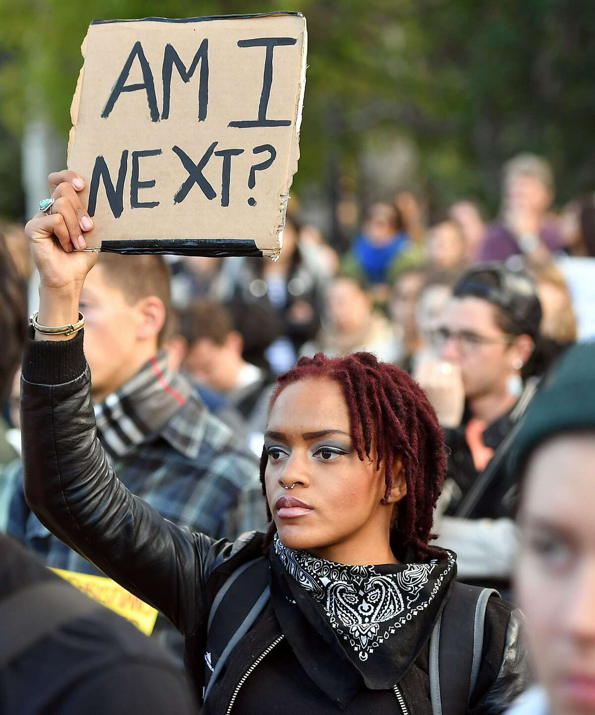 A woman holds up a sign during a rally at Justin Herman Plaza to denounce recent police shootings around the country, in San Francisco, California on July 8, 2016. Thousands of protesters took to the streets in US cities on July 8 after a black extremist shot dead five cops during a peaceful march against police brutality in Texas. / AFP PHOTO / Josh EdelsonJOSH EDELSON/AFP/Getty Images