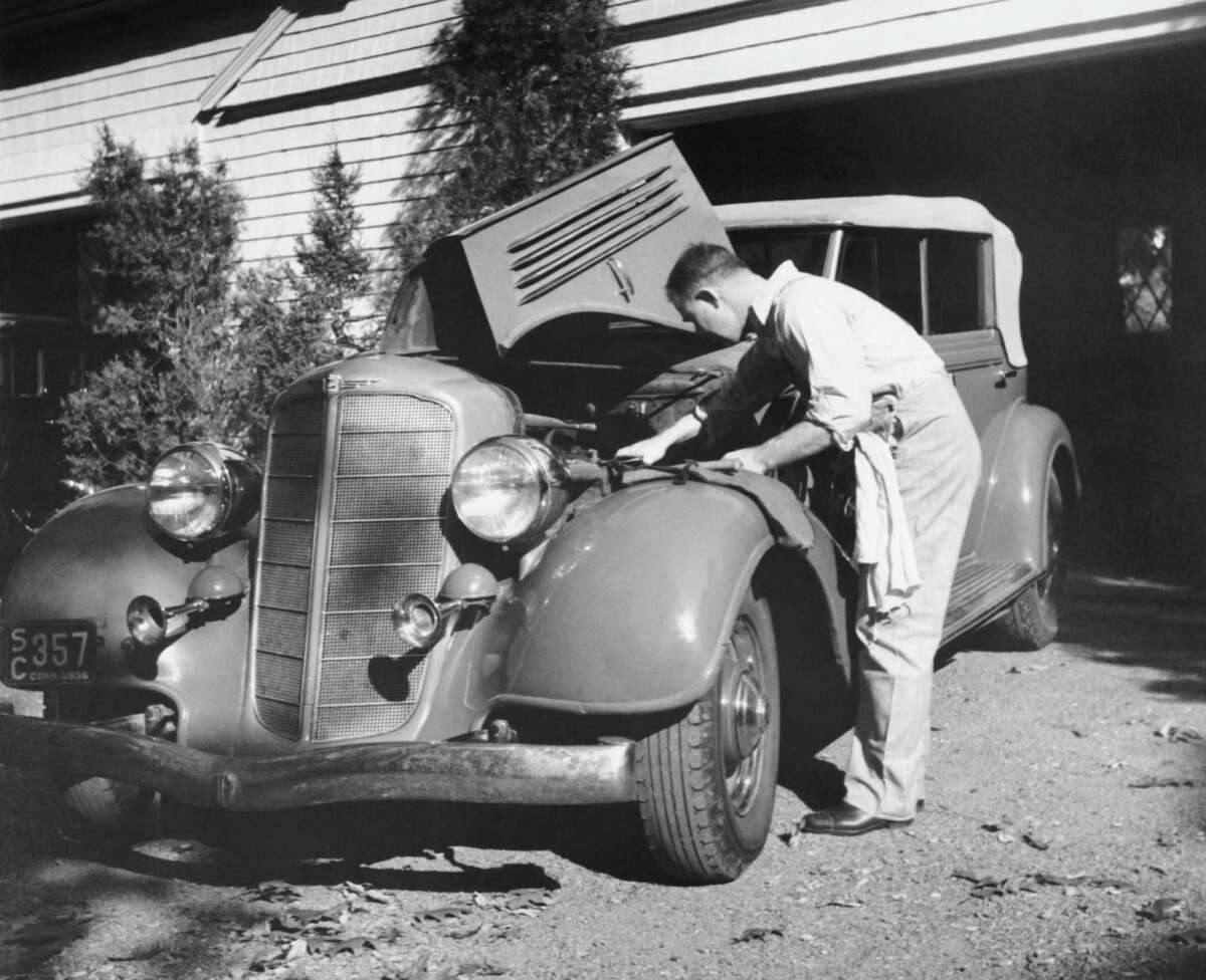 A man working on his car in front of his garage, Connecticut, 1936.