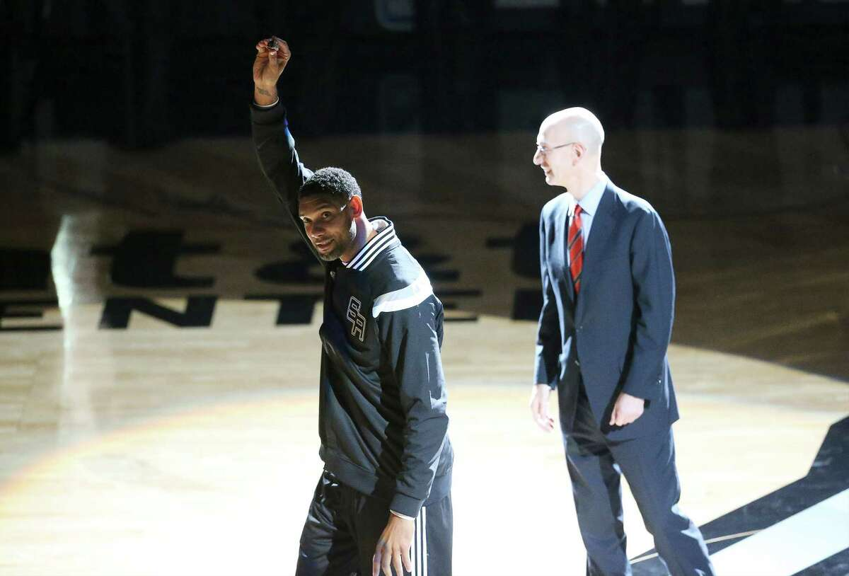 Spurs' Tim Duncan shows his 2014 NBA Championship ring to the fans during the ring ceremony and season opener against the Dallas Mavericks at the AT&T Center on Tuesday, Oct. 28, 2014. (Tom Reel/San Antonio Express-News)