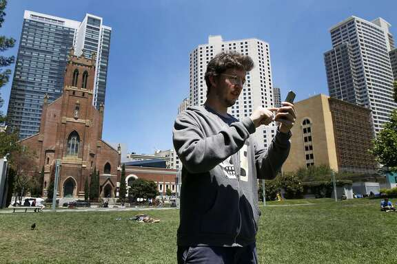 Adam Williams plays Pokemon Go during his lunch break at Yerba Buena Gardens in San Francisco, California, on Monday, July 11, 2016.