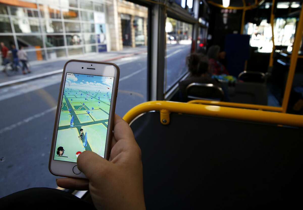 A woman plays Pokemon Go while riding on a bus through downtown San Francisco, California, on Monday, July 11, 2016.