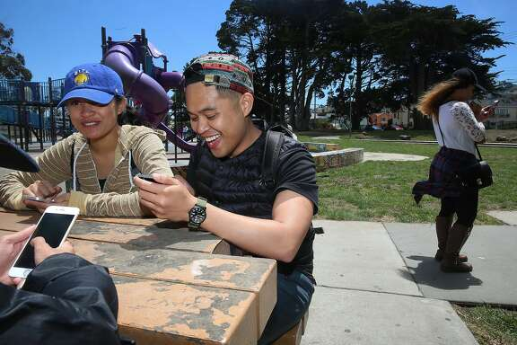 Kristina Liwanag (blue cap), 22 years old, and Greg Pancho (next to Liwanag), 27 years old,  and Mechelle Latitan (far left), catch lures playing Pokemon Go at Crocker Amazon park on Monday, July 11, 2016 in San Francisco, Calif.
