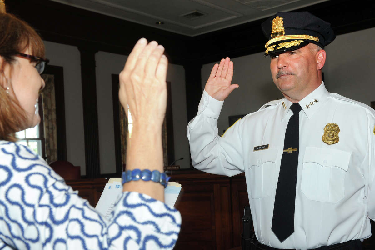 Joseph McNeil is sworn in as Stratford's new Chief of Police during a ceremony at Town Hall in Stratford, Conn. July 11, 2016. McNeil takes the oath from Town Clerk Susan Pawluk.
