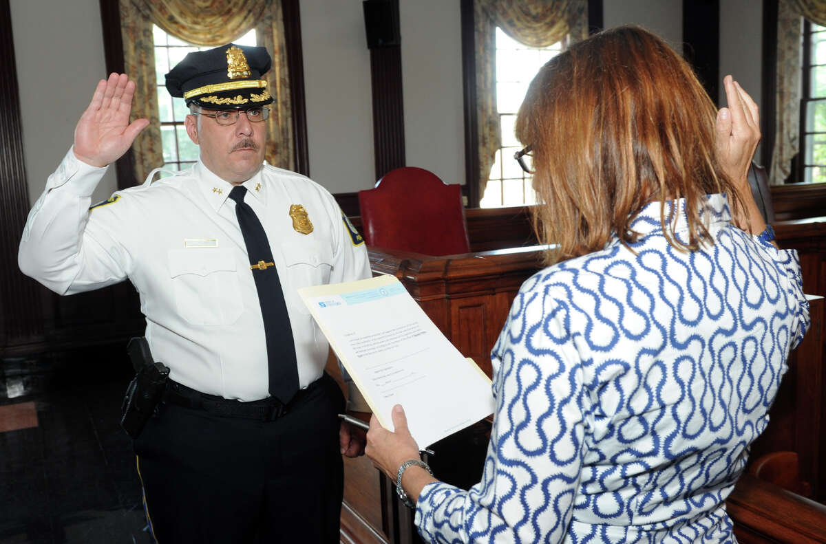 John Popik is sworn is as Stratford's new Deputy Police Chief during a ceremony at Town Hall in Stratford, Conn. July 11, 2016. Popik takes the oath from Town Clerk Susan Pawluk.