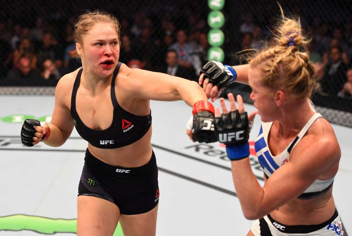 Ronda Rousey (left) punches Holly Holm in their UFC women's bantamweight championship bout during the UFC 193 event at Etihad Stadium on November 15, 2015 in Melbourne, Australia.