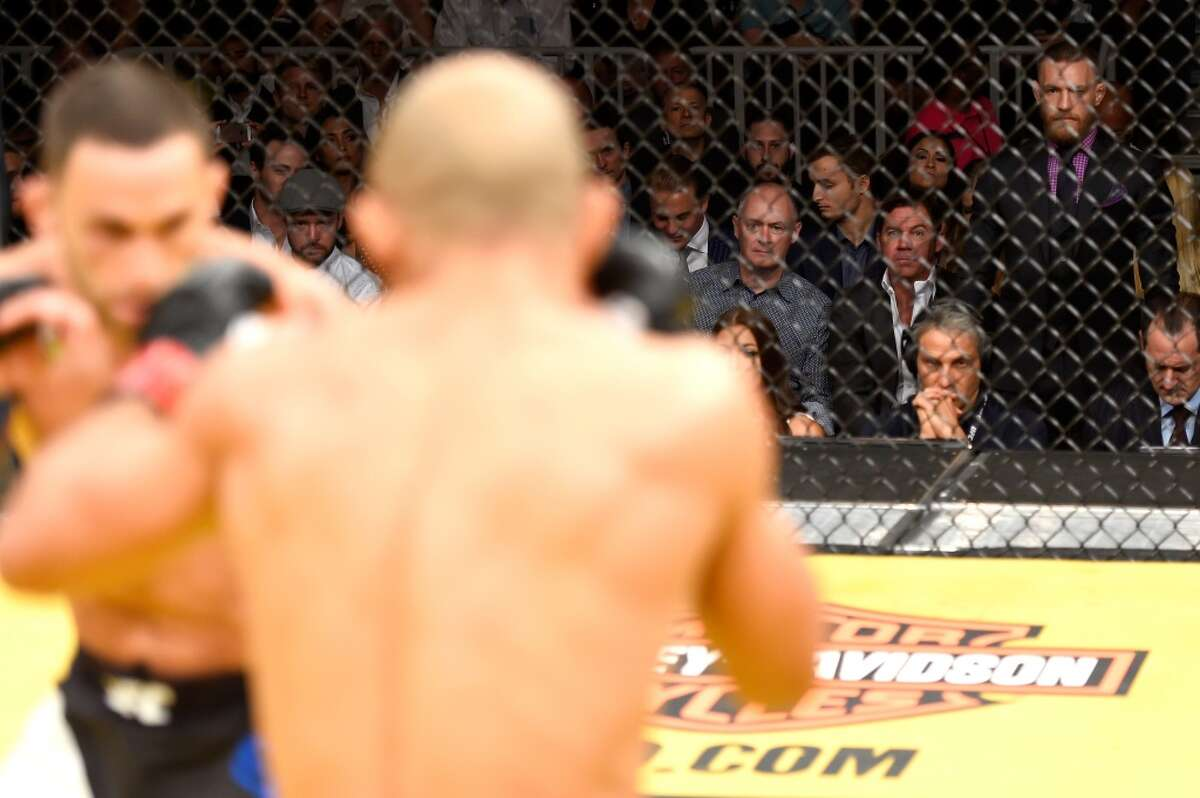 This photo of UFC featherweight champion Conor McGregor (right) watching Jose Aldo of Brazil vs Frankie Edgar in their UFC interim featherweight championship bout during the UFC 200 event on July 9 has got everyone talking. Is he mad dogging the athletes, or just concentrating hard on the match?