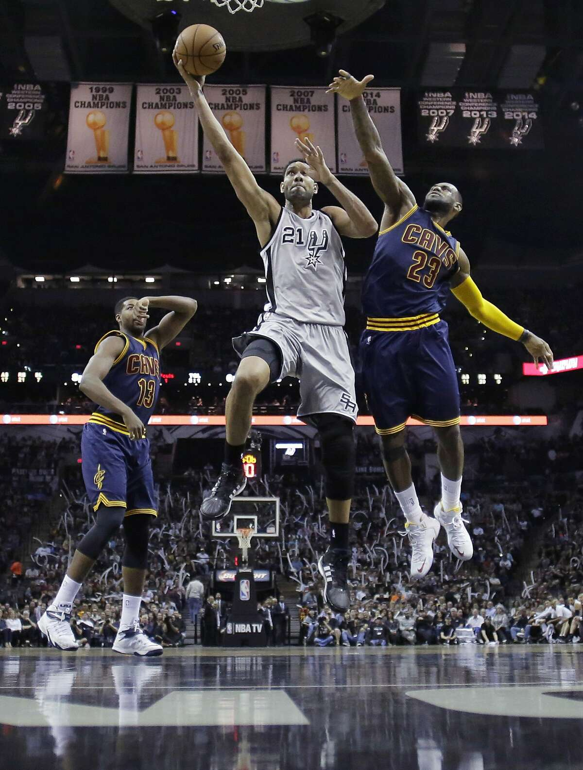 FILE - In this March 13, 2015, file photo, San Antonio Spurs' Tim Duncan (21) shoots next to Cleveland Cavaliers' LeBron James (23) during the second half of an NBA basketball game in San Antonio. Duncan announced his retirement on Monday, July 11, 2016, after 19 seasons, five championships, two MVP awards and 15 All-Star appearances. It marks the end of an era for the Spurs and the NBA. (AP Photo/Eric Gay, File)