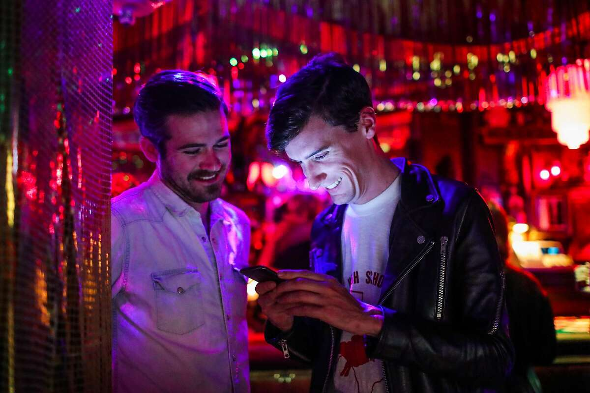 Steven Fromtling (left) and Matt Barnes (right) look at a phone together while having a drink at The Stud Bar in San Francisco, California, on Friday, July 8, 2016.