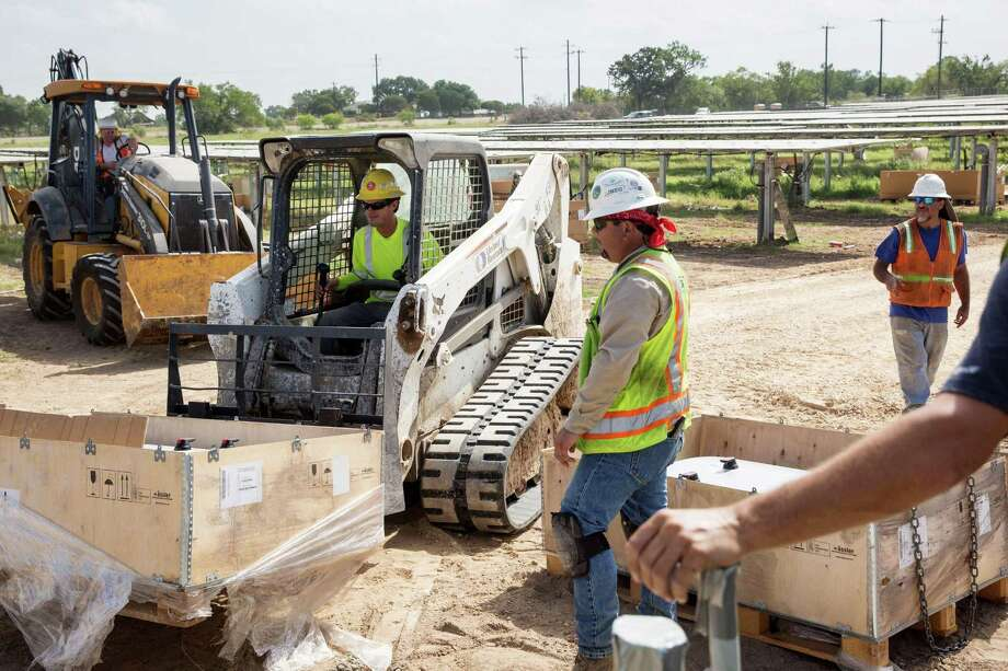 Construction workers prepare to install an inverter at a solar farm in Adkins. A new study shows that solar jobs in Bexar County increased from 572 in 2015 to 1,665 in 2016, accounting for nearly half the solar job growth in Texas for 2016. Photo: Ray Whitehouse /For The San Antonio Express-News