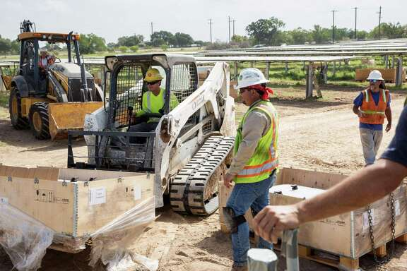 Construction workers prepare to install an inverter at a solar farm in Adkins. A new study shows that solar jobs in Bexar County increased from 572 in 2015 to 1,665 in 2016, accounting for nearly half the solar job growth in Texas for 2016.