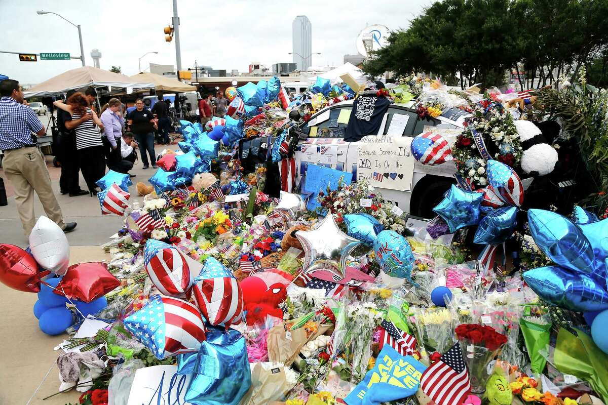 A memorial to fallen police officers grows in front of the Jack Evans Police Headquarters building in Dallas on Monday. Most of Dallas got back to work at the start of the week following an emotional and stress-filled weekend.