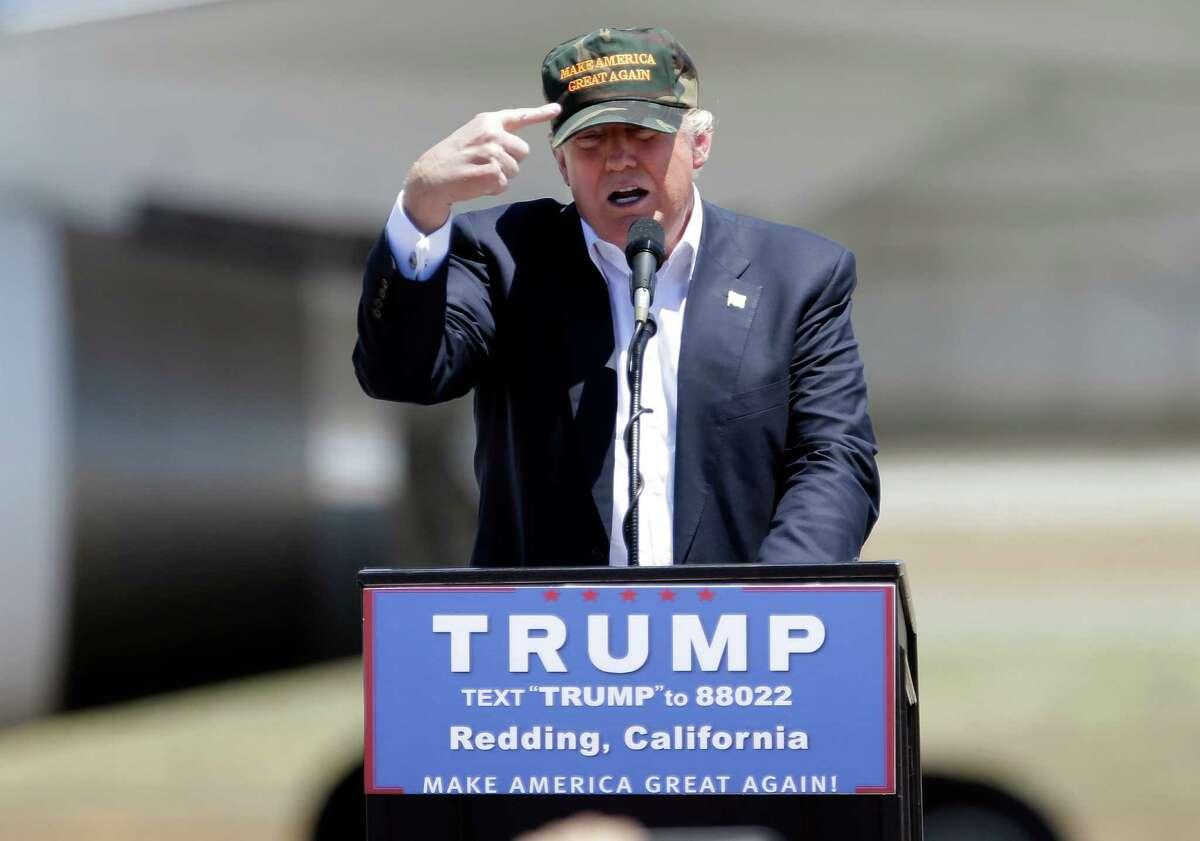 """In this June 3, 2016 file photo, Republican presidential candidate Donald Trump gestures to a his camouflaged """"Make America Great"""" hat at a campaign rally at the Redding Municipal Airport in Redding, Calif."""