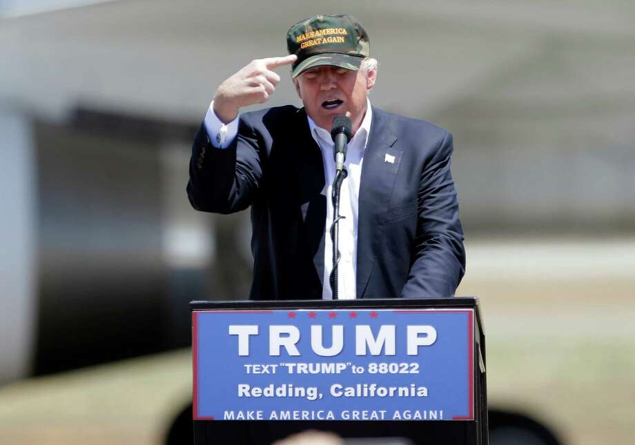 """In this June 3, 2016 file photo, Republican presidential candidate Donald Trump gestures to a his camouflaged """"Make America Great"""" hat at a campaign rally at the Redding Municipal Airport in Redding, Calif. Photo: Rich Pedroncelli, AP / Copyright 2016 The Associated Press. All rights reserved. This material may not be published, broadcast, rewritten or redistribu"""
