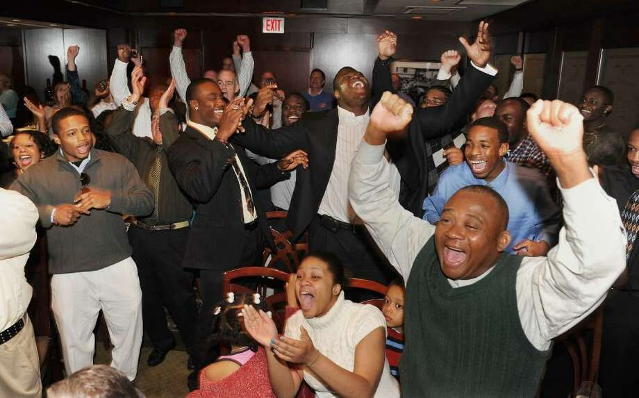 Family and friends rejoice after hearing the news that Vlad Ducasse, back center with arm in air, has been drafted to the New York Jets, during the NFL draft pick gathering at Morton's Steakhouse in downtown Stamford, Conn. on Friday April 23, 2010. Photo: Christian Abraham, ST / Connecticut Post