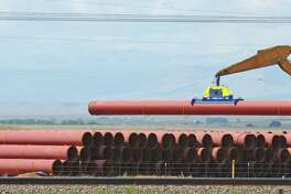 """Pipe is stacked for the construction of a section of a Kinder Morgan pipeline near Laramie, Wyo. Rich Kinder said Monday that the company is """"measurably closer to being able to return dollars to our shareholders through increased dividends or buying back stock."""""""