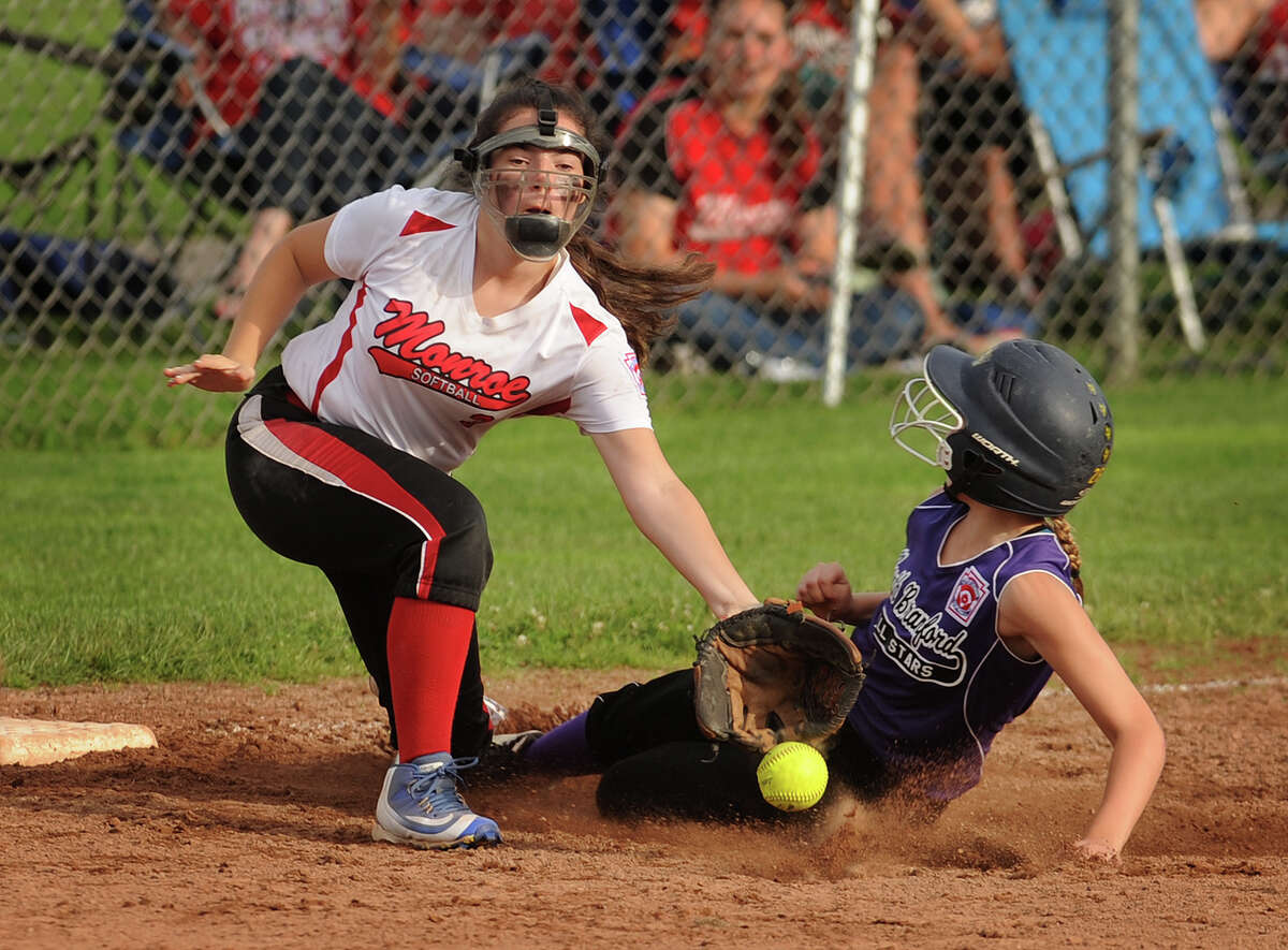 North Branford's Erica Piercey steals third base ahead of the throw to Monroe third baseman Britney Berg before going on to score her team's second run in the fifth inning of their 3-0 victory in the Section 1 Little League softball championship game at Unity Park in Trumbull on Monday.