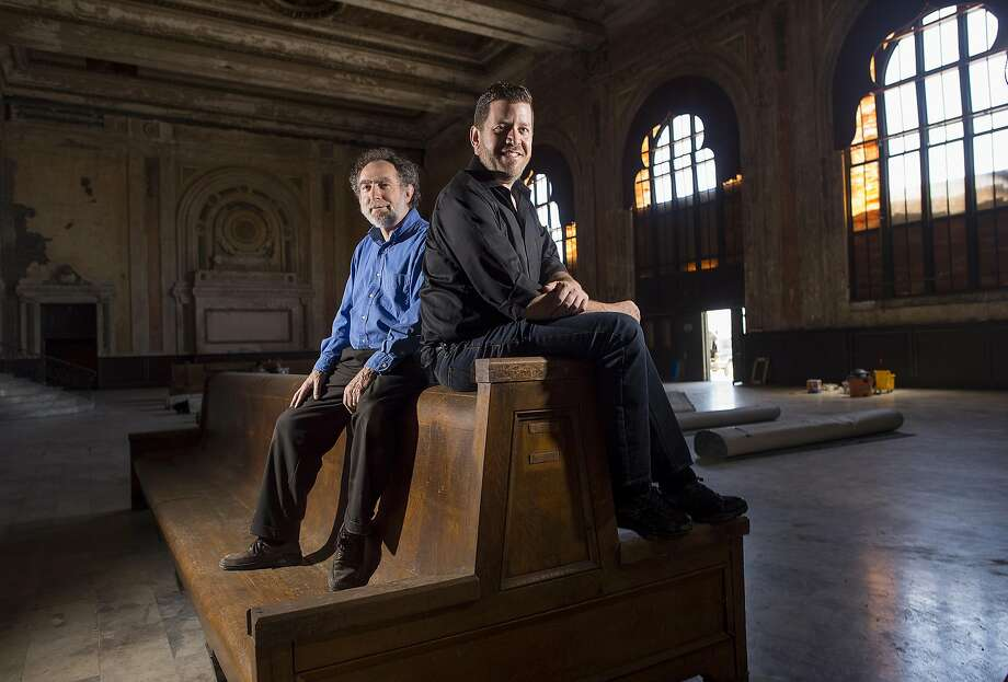 West Edge Opera artistic director Mark Streshinsky, right, and music director Jonathan Khuner sit on a historic bench at the Oakland 16th Street Station on Monday, July 11, 2016, in Oakland, Calif. Their company will stage three operas this summer at the long vacant rail station. Photo: Noah Berger, Special To The Chronicle