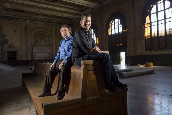 West Edge Opera artistic director Mark Streshinsky, right, and music director Jonathan Khuner sit on a historic bench at the Oakland 16th Street Station on Monday, July 11, 2016, in Oakland, Calif. Their company will stage three operas this summer at the long vacant rail station.