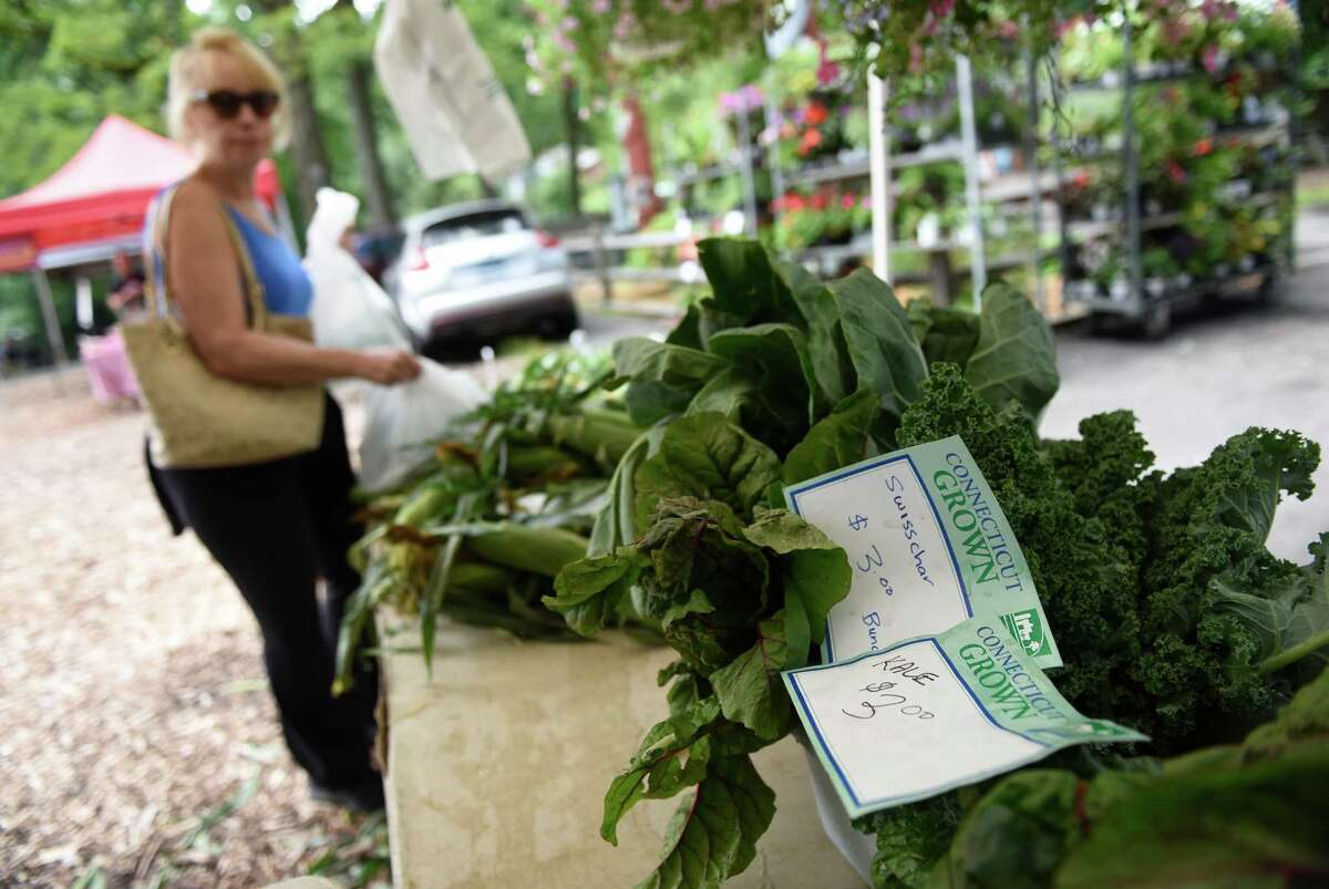 Folks browse the Connecticut Grown stand at the Stamford Museum & Nature Center's Farmers' Market in Stamford, Conn. Sunday, July 10, 2016. The market features a variety of local vendors, ranging from produce to soap, and runs every Sunday from 10 a.m. to 2 p.m. through October 9.