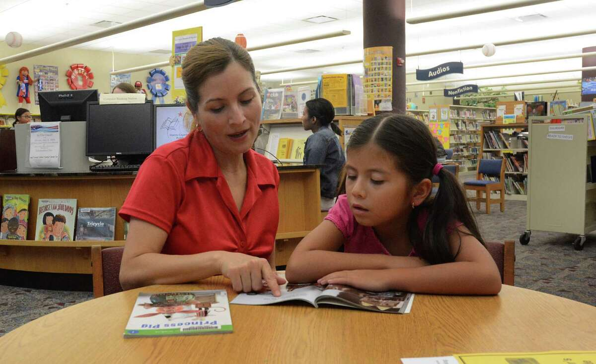 Marcelina Rodriquez and her daughter, Naylei, work together on summer reading at the Barbara Bush Library, 6817 Cypresswood Drive in Spring.