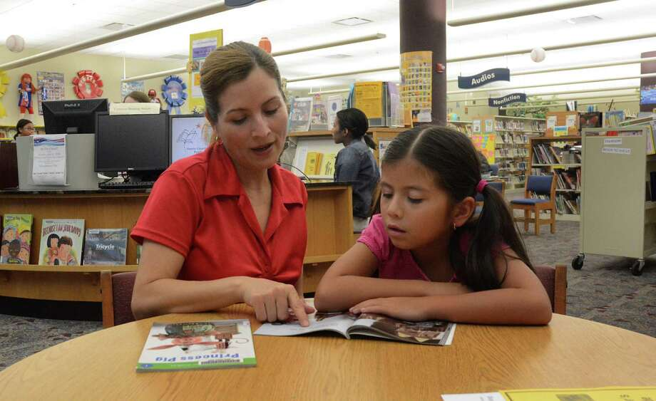 Marcelina Rodriquez and her daughter, Naylei, work together on summer reading at the Barbara Bush Library, 6817 Cypresswood Drive in Spring. Photo: Z-David Hopper
