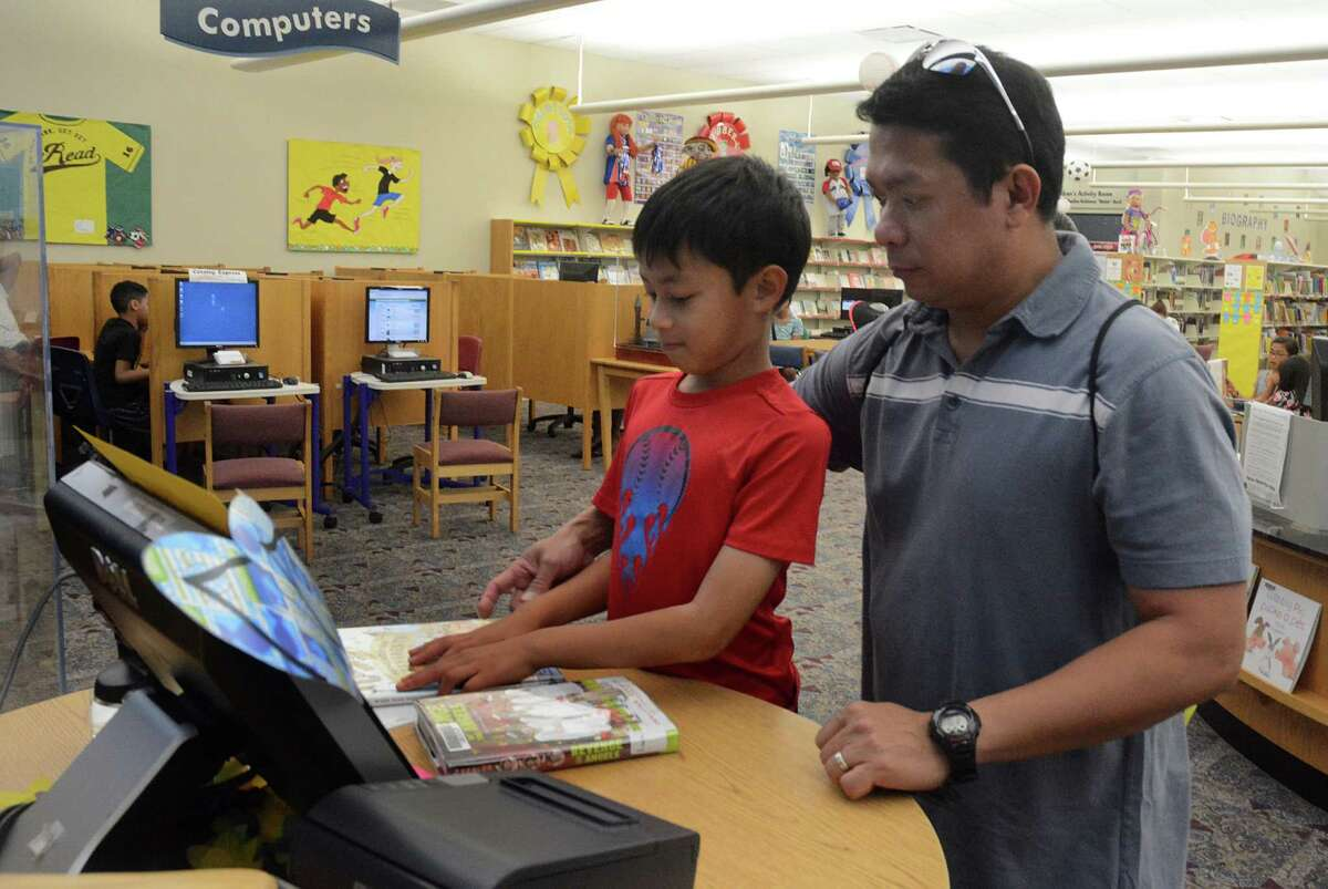 Angelo Dujunco shows his dad, Michael, how to use the book check out computer in the children's library at the Barbara Bush Library, 6817 Cypresswood Drive in Spring.