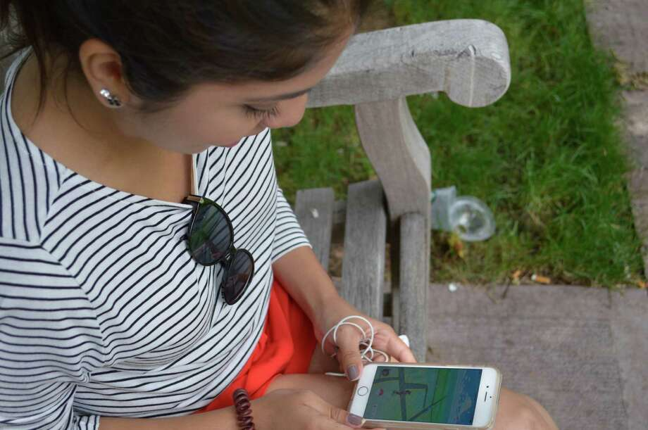 Stephanie Sanchez, 25, checks her phone for local Pokemon in the park on Greenwich Avenue on her lunch break from Ralph Lauren. Photo: Jennifer Turiano / Hearst Connecticut Media / Greenwich Time
