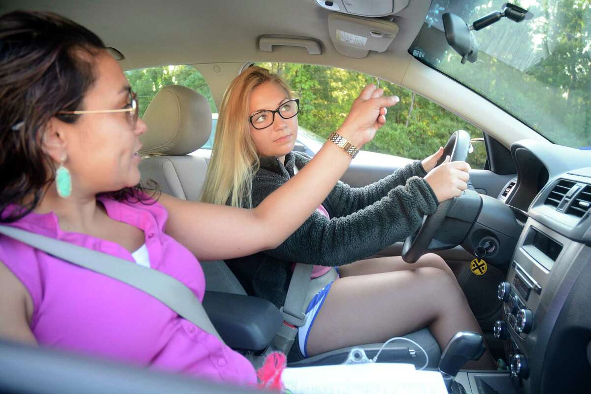Driver's education instructor Jessica Vargas reminds Julia Bowden of The Woodlands to check her mirror before driving during a recent driver's education class at The Woodlands High School.