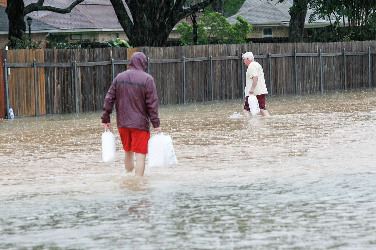 Residents carry ice to a home in Old Katy just off First Street and Caroline after torrential rains caused massive flooding in parts of the city on April 18, 2016. Residents said that the area had not flooded since 1985.Residents carry ice to a home in Old Katy just off First Street and Caroline after torrential rains caused massive flooding in parts of the city on April 18, 2016. Residents said that the area had not flooded since 1985.
