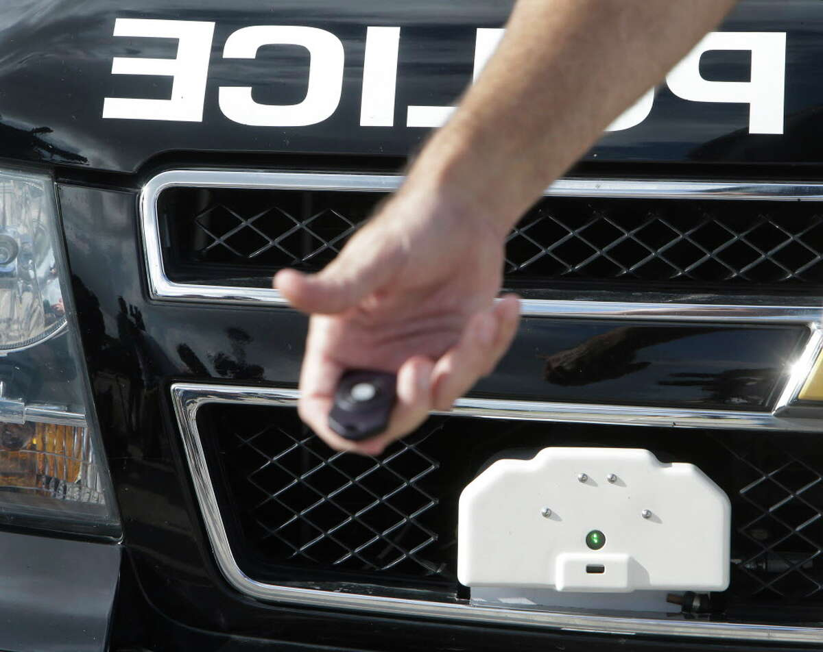 Houston Police Sgt James Turner holds a remote used to fire the StarChase System, a vehicle pursuit technology, that is shown attached to the grill area of a police vehicle during testing at the driving track of the Houston Police Academy L. D. Morrison Sr. Memorial Center, Tuesday, July 12, 2016, in Houston. The StarChase System device is launched at a fleeing vehicle from the front of a police unit and contains a GPS transmitter.