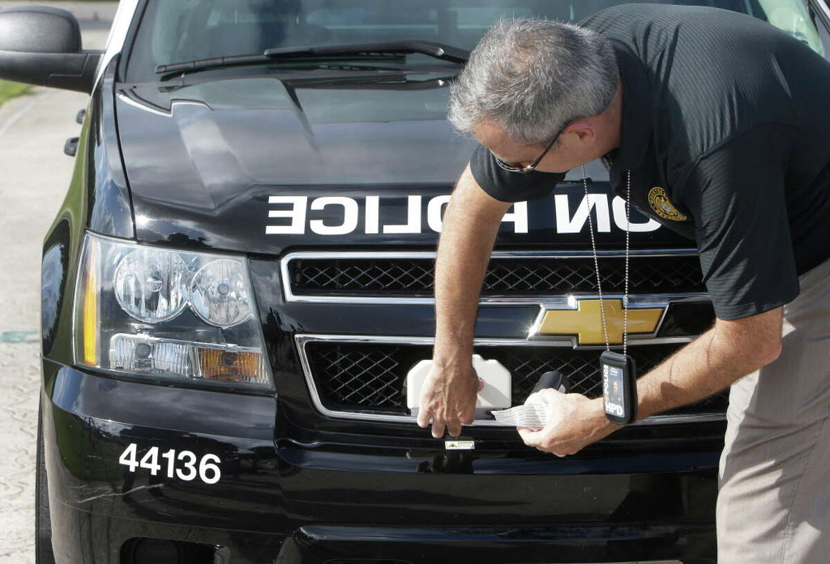 Houston Police Sgt. James Turner reloads the StarChase System, a vehicle pursuit technology, attached to the grill area of a police vehicle during testing at the driving track of the Houston Police Academy L. D. Morrison Sr. Memorial Center, Tuesday, July 12, 2016, in Houston. The StarChase System device is launched at a fleeing vehicle from the front of a police unit and contains a GPS transmitter.