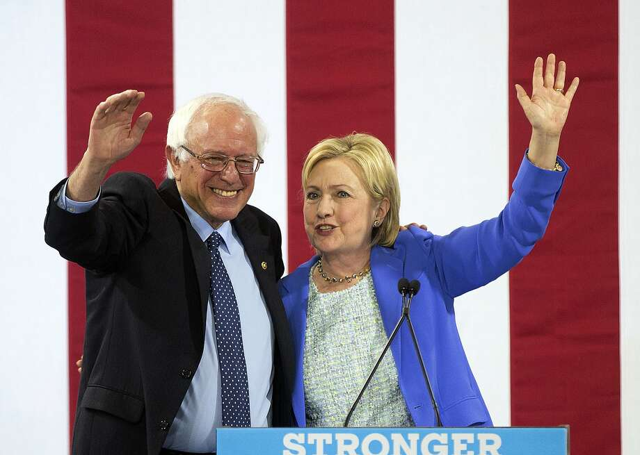Hillary Clinton waves to supporters with Sen. Bernie Sanders, I-Vt., during a rally in Portsmouth, N.H., where Sanders endorsed her for president. Photo: Jim Cole, Associated Press