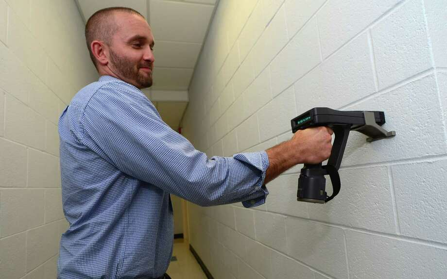 Shaun Duffy, a registered sanitarian with the Norwalk Department of Health, tests the XRF Lead Paint Analysis System on a cinder block wall Friday. Photo: Erik Trautmann / Hearst Connecticut Media