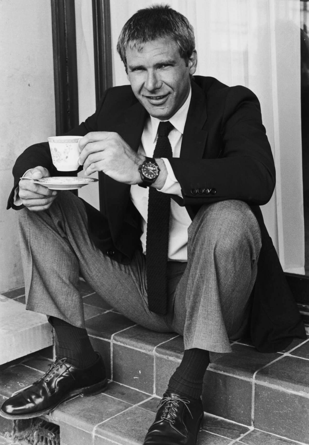 Click through this gallery to see Harrison Ford through the years. circa 1984: American actor Harrison Ford sits on steps, smiling while holding a teacup and saucer.