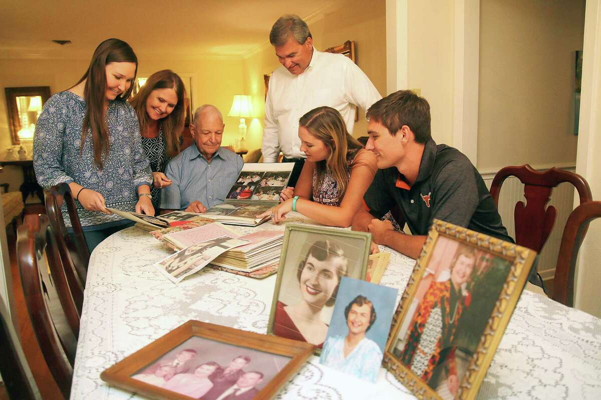 Gathered in the dining room looking over photos of Betty Nelson are her family Emily Nelson, left, granddaughter; Carol Nelson, daughter-in-law; Bob Nelson, husband; Bill Nelson, son; Katie Nelson, granddaughter, and Rob Nelson, grandson.