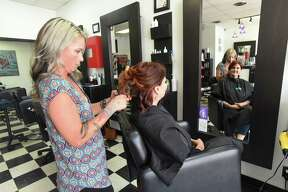 Stylist Genevieve Garcia works on customer Stacy Deltora at Moxie Hair Salon, winner of the Readers' Choice Award for Hair Salon.