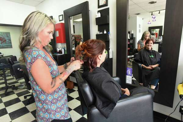 Stylist Genevieve Garcia works on customer Stacy Deltora at Moxie Hair Salon, winner of the Readers' Choice Award for Hair Salon.