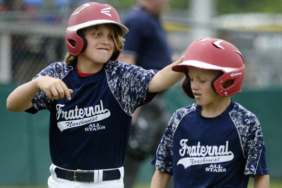 Fraternal Northwest's Jack Malecki, left, pats teammate Drew Ieuter on the head after Ieuter's run against Shepherd during the inning on Saturday at Mark Smit Field. Fraternal Northwest won 15-5. Photo: Nick King/Midland  Daily News/Nick King