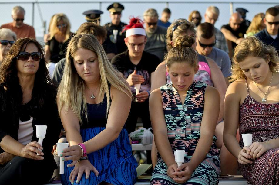 From left, Katy Sherwood, her daughters Meagan, 22, Gwen, 13 and Gabby, 16, bow their heads during a prayer during a vigil on Monday at the Midland County Fairgrounds. Katy's husband and her daughters' father Clare County Deputy Kevin M. Sherwood was killed in the line of duty in 2003. The Midland County SheriffÕs Office Community Awareness Team planned the vigil tonight for the victims of an ambush that left five police officers dead and seven wounded in Dallas. Photo: Nick King/Midland  Daily News/Nick King