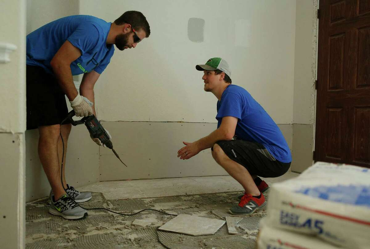 Jarod Palmer (right) gets help from neighbor Zach White removing tile Thursday, June 30, 2016, after recent flooding poured inches of water into their home in Fort Bend County. ( Mark Mulligan / Houston Chronicle )