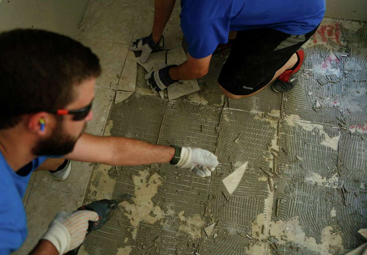 Jarod Palmer (top) gets help from neighbor Zach White (left) removing tile Thursday, June 30, 2016, after recent flooding poured inches of water into their home in Fort Bend County. ( Mark Mulligan / Houston Chronicle )