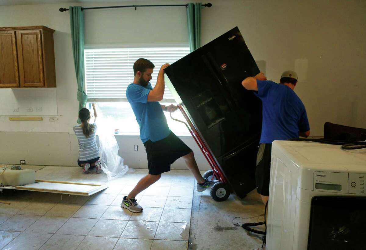 Jarod Palmer (right) gets help from neighbor Zach White (center) removing tile Thursday, June 30, 2016, after recent flooding poured inches of water into their home in Fort Bend County. ( Mark Mulligan / Houston Chronicle )