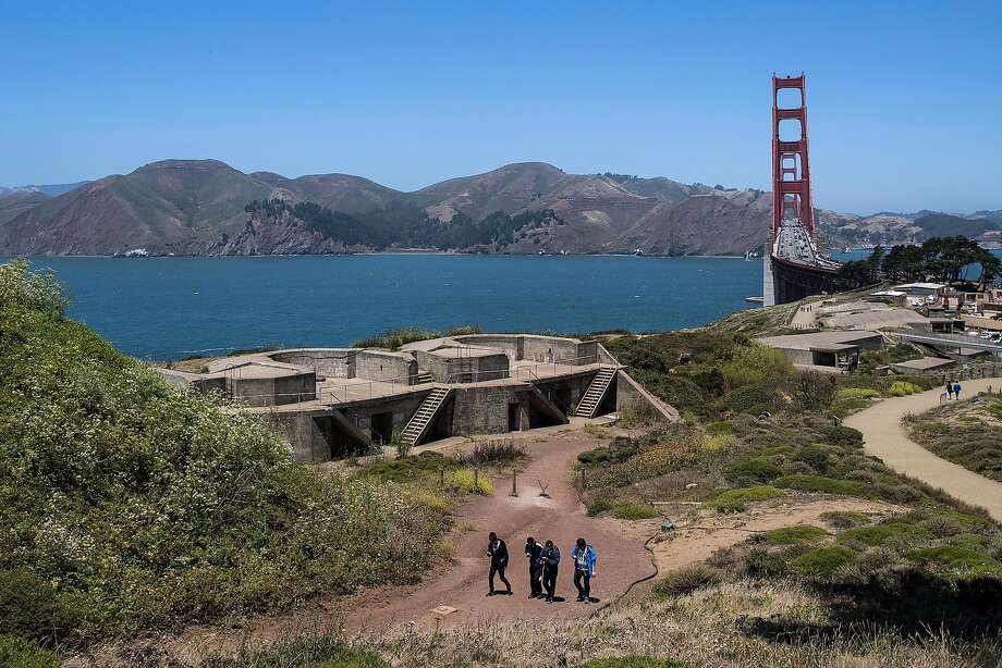 The Marin Headlands and the Golden Gate Bridge serve as a backdrop to a group walking past Battery Godfrey in the Presidio. Jean Fraser, below, former CEO of the San Francisco Health Plan, is the new leader of the Presidio Trust. Photo: Stephen Lam, Special To The Chronicle