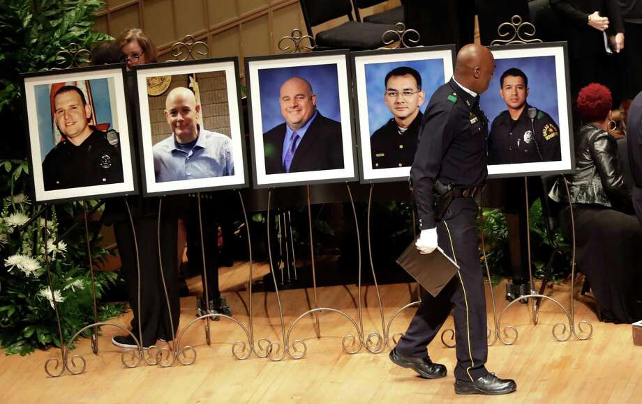 A member of the Dallas Police Choir passes the portraits of five fallen officers prior to a memorial service at the Morton H. Meyerson Symphony Center, Tuesday, July 12, 2016, in Dallas. Five police officers were killed and several injured during a shooting in downtown Dallas last Thursday night. (AP Photo/Eric Gay) Photo: Eric Gay, STF / Copyright 2016 The Associated Press. All rights reserved. This material may not be published, broadcast, rewritten or redistribu
