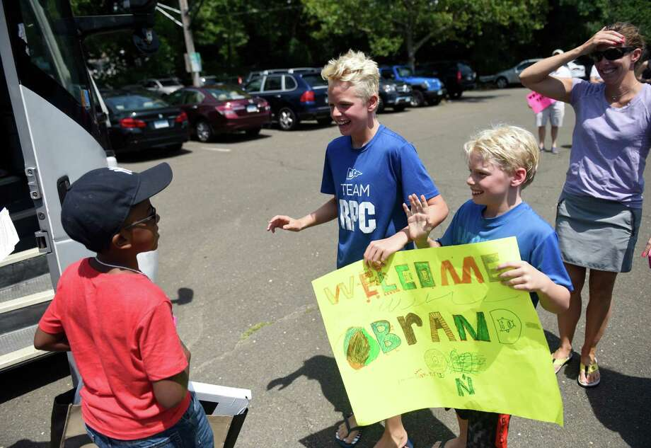Bronx, N.Y. resident Obrando Silverio, left, 10, is greeted by his Old Greenwich host family, Luke Nelson, center, 11, Austin Nelson, 9, and Allison Nelson as children from New York City arrive to greet their Fresh Air Fund host families at the train station in Old Greenwich, Conn. Tuesday, July 12, 2016. The Fresh Air Fund provides inner city children with a week-long experience staying with a host family outside of the city, with several host families located in Greenwich. New York City children ages seven to 18 get to experience small town pleasures and nature outside the city while building a relationship with host parents and making new friends. Photo: Tyler Sizemore / Hearst Connecticut Media / Greenwich Time