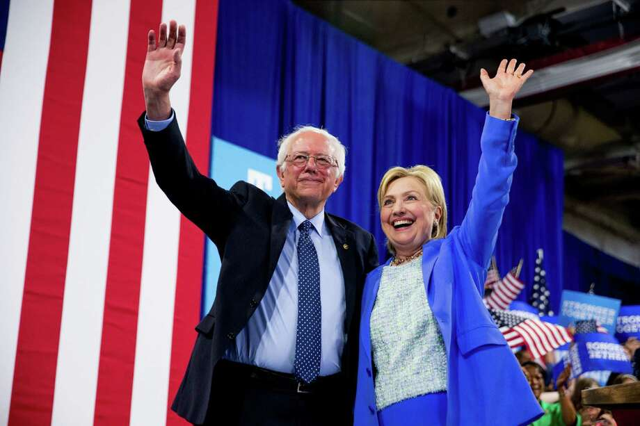 Democratic presidential candidate Hillary Clinton and Sen. Bernie Sanders, I-Vt., wave to supporters during a rally in Portsmouth, N.H., on Tuesday, where Sanders endorsed Clinton. Photo: Andrew Harnik, STF / Copyright 2016 The Associated Press. All rights reserved. This material may not be published, broadcast, rewritten or redistribu
