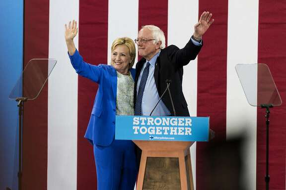 Hillary Clinton, presumptive 2016 Democratic presidential nominee, and Senator Bernie Sanders, an independent from Vermont and 2016 Democratic presidential candidate, wave while on stage during a campaign event in Portsmouth, New Hampshire, U.S., on Tuesday, July 12, 2016. Sanders joined most of the rest of the Democratic Party on Tuesday by formally endorsing Clinton, a step toward unity motivated as much by fear of a Donald Trump presidency as ardor for the presumptive nominee. Photographer: Ian Thomas Jansen-Lonquist/Bloomberg